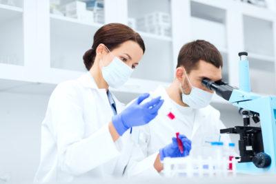 Zwei qualifizierte Wissenschaftler mit Pipette, Teströrchen und Mikroskop im Labor